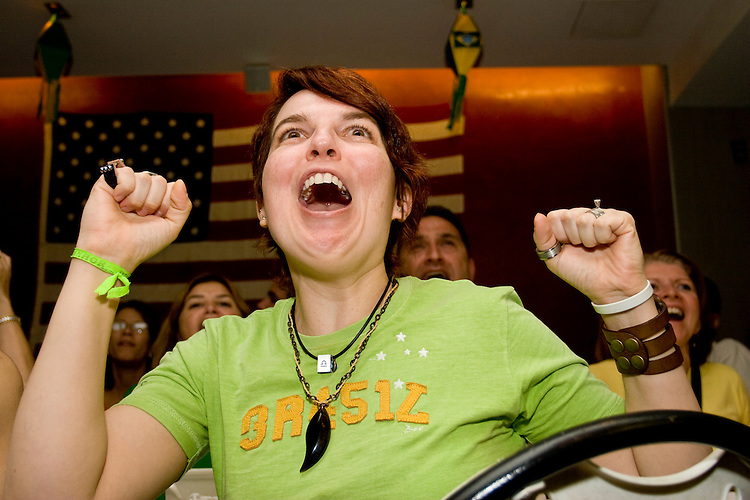 """Brazil fan Marilia Vieire cheers on her team in a match against Australia on June 18, 2006 at the Emporium, a restaurant in a section of New York City known as """"Little Brazil"""".<br /> <br /> The World Cup, held every four years in different locales, is the world's pre-eminent sports tournament in the world's most popular sport, soccer (or football, as most of the world calls it).  Qualification for the World Cup is open to any country with a national team accredited by FIFA, world soccer's governing body. The first World Cup, organized by FIFA in response to the popularity of the first Olympic Games' soccer tournaments, was held in 1930 in Uruguay and was participated in by 13 nations.    <br /> <br /> As of 2010 there are 208 such teams.  The final field of the World Cup is narrowed down to 32 national teams in the three years preceding the tournament, with each region of the world allotted a specific number of spots.  <br /> <br /> The World Cup is the most widely regularly watched event in the world, with soccer teams being a source of national pride.  In most nations, the whole country is at a standstill when their team is playing in the tournament, everyone's eyes glued to their televisions or their ears to the radio, to see if their team will prevail.  While the United States in general is a conspicuous exception to the grip of World Cup fever there is one city that is a rather large exception to that rule.  In New York City, the most diverse city in a nation of immigrants, the melting pot that is America is on full display as fans of all nations gather in all possible venues to watch their teams and celebrate where they have come from."""