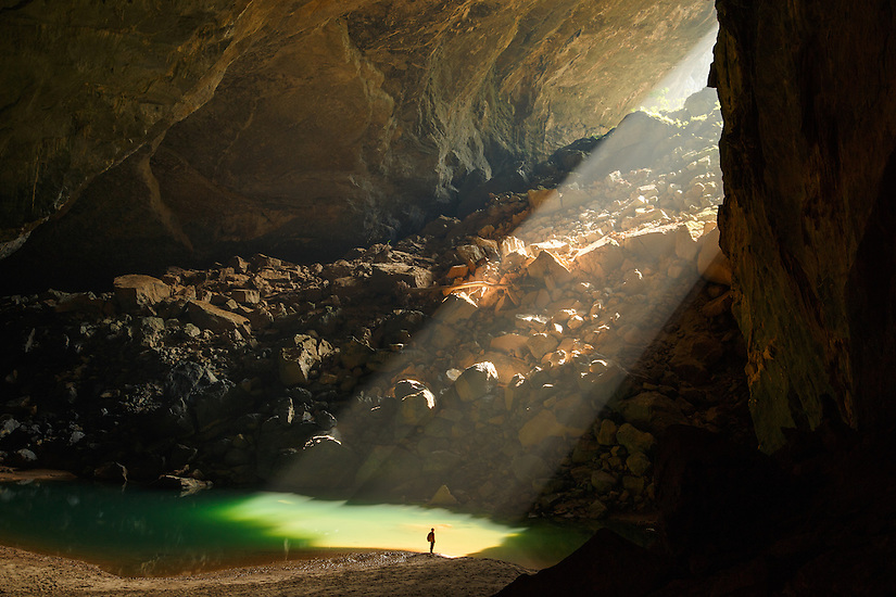 A sunbeam shines in on a caver through an entrance of En Cave, Vietnam.