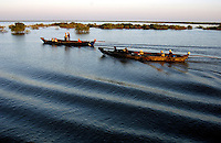 CRUISING THE TONLE SAP LAKE IN CAMBODIA, TRADITIONAL BOATS AT SUNSET