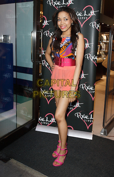 DIONNE BROMFIELD.At the Pixie Lott for Lipsy Party, Swarovski Crystallized Boutique, London, England, UK, April 21st 2011..full length peach pink purple shorts print top belt hand on hip sandals waist t-bar blue .CAP/ROS.©Steve Ross/Capital Pictures