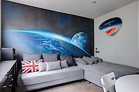 A teenagers bedroom with a single bed and sofa and a grey storage unit. A striking image of the earth takes up one wall.