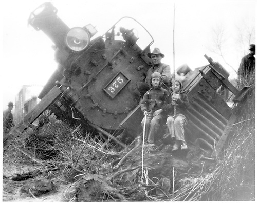 #375 derailed.  A man and two children are sitting on front of engine.<br /> D&amp;RGW  Durango, MP 452.40, CO  1930
