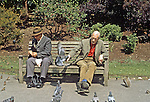 Two gentlemen sharing a park bench and feeding the wildlife in Dulich Park, London, England.