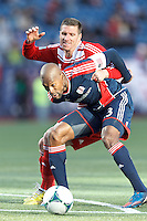 In the box, New England Revolution defender Jose Goncalves (23) shields ball from FC Dallas forward Kenny Cooper (33)..  In a Major League Soccer (MLS) match, FC Dallas (red) defeated the New England Revolution (blue), 1-0, at Gillette Stadium on March 30, 2013.