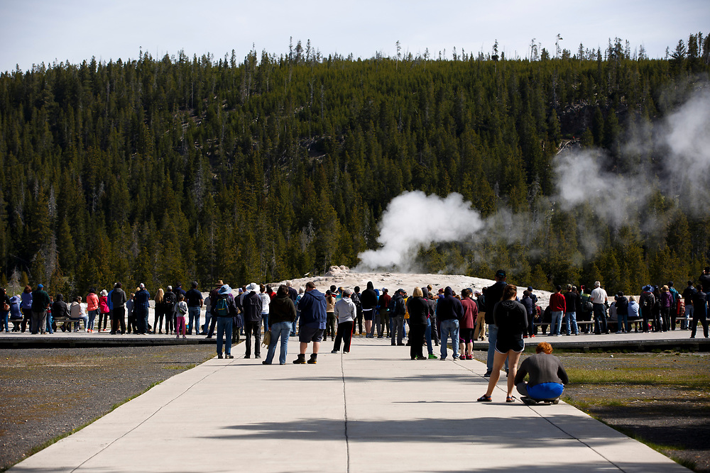 Tourists wait for an eruption from Old Faithful in Yellowstone National Park, Wyoming on Tuesday, May 23, 2017. (Photo by James Brosher)