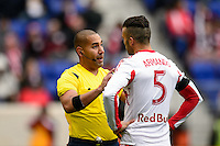 Referee Juan Guzman talks with Armando (5) of the New York Red Bulls. The New York Red Bulls and Chivas USA played to a 1-1 tie during a Major League Soccer (MLS) match at Red Bull Arena in Harrison, NJ, on March 30, 2014.