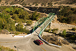 A red car crosses a green painted double-arch truss bridge carries a country road over the Arroyo Seco wash in the Salinas Valley.