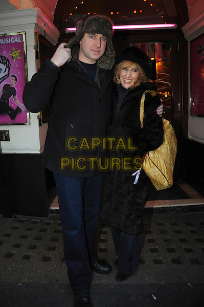 "TIM VINE & ANITA DOBSON .Leaving after a performance of ""Grease"" the musical, Piccadilly Theatre, London, England, UK, 26th November 2010..full length hat black coat fur bag gloves arm around jeans jacket deer stalker .CAP/IA.©Ian Allis/Capital Pictures."