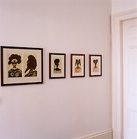 A series of portrait paintings by Chris Ofili line the hall wall