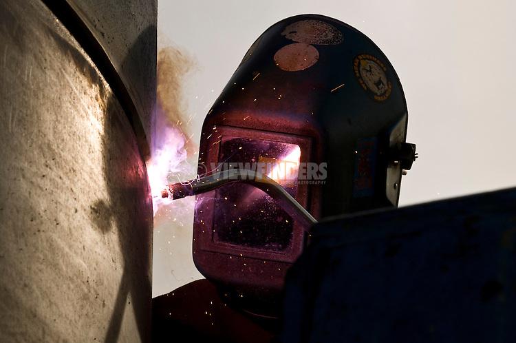 Man welding at a construction site.
