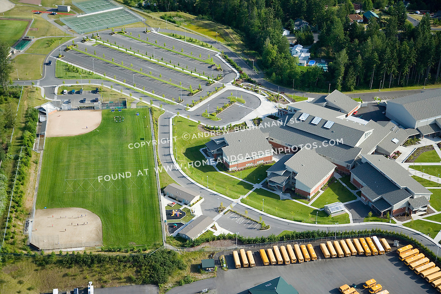 Aerial view of a large, suburban, public high school in Bonney Lake, Washington with yellow school buses lining the edge of the property