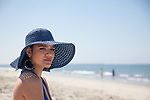 Young brunette woman with  blue hair  and a blue hat in a blue dress at the beach