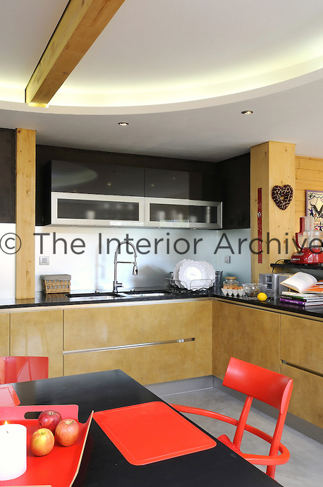 This kitchen has been designed using the Chinese practice of feng shui, the units and work surfaces enclose a black table accompanied by red chairs, chosen to bring good fortune