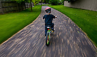 Young boy wearing safety helmet rides his bicycle along path through his neighborhood.  Photo Copyright Gary Gardiner. Not be used without written permission detailing exact usage.