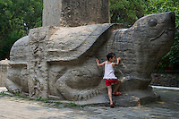 Chinese girl stands by Bixi(stone tortoise) carrying tablets at Dai Temple in Taishan Mountain, Shandong, China. Dai Temple is a Taoist temple as well as the largest and best-preserved architectural complex on Mt. Taishan..10 Jul 2011