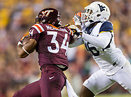 Landover, MD - SEPT 3, 2017: Virginia Tech Hokies running back Travon McMillian (34) stiff arms West Virginia Mountaineers safety Toyous Avery (16) after a big run during game between West Virginia and Virginia Tech at FedEx Field in Landover, MD. (Photo by Phil Peters/Media Images International)