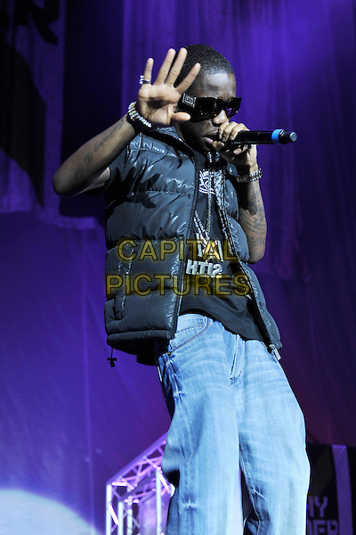 TINCHY STRYDER (Kwasi Danquah).Live at the O2 Arena, London, England, UK, 3rd February 2011..music concert live on stage concert gig  performing half length microphone singing rapping black puffa puffer bodywarmer jeans hand sunglasses .CAP/MAR.© Martin Harris/Capital Pictures.