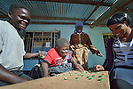 Peter Makura plays a board game with friends in the village of Berejena, near Masvingo, Zimbabwe. The Jairos Jiri Association provided Makura with his wheelchair with support from CBM-US.