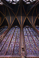 View from below of the clerestories of the nave in the upper chapel of La Sainte-Chapelle (The Holy Chapel), 1248, Paris, France. Fifteen huge mid-13th century windows fill the nave and apse. Each window group has four lancets topped by three rose windows. At the bottom, a statue of apostle can be seen. La Sainte-Chapelle was commissioned by King Louis IX of France to house his collection of Passion Relics, including the Crown of Thorns, and is considered among the highest achievements of the Rayonnant period of Gothic architecture. Picture by Manuel Cohen