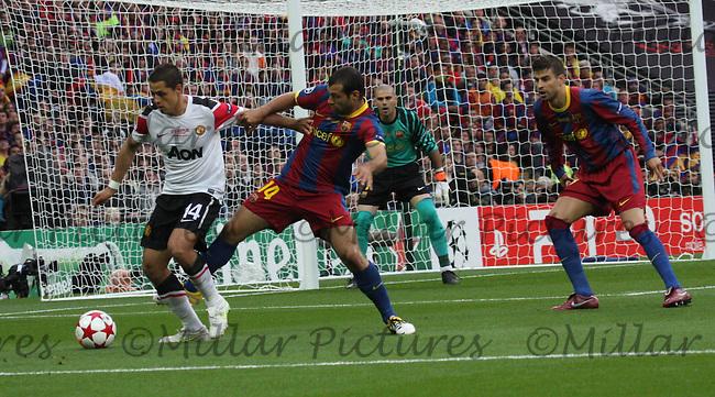 Javier Hernandez being put under pressure by Javier Mascherano as Gerard Pique looks on
