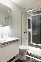 A mosaic tiled bathroom with a simple glass shower unit and white bathroom furniture and minimal recessed lighting