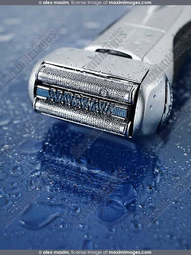 High-end electric foil shaver on wet blue glass background with water drops on it