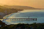 Golden sunrise light over coastal hills, pier, and beach at Gaviota Beach State Park, near Santa Barbara, California