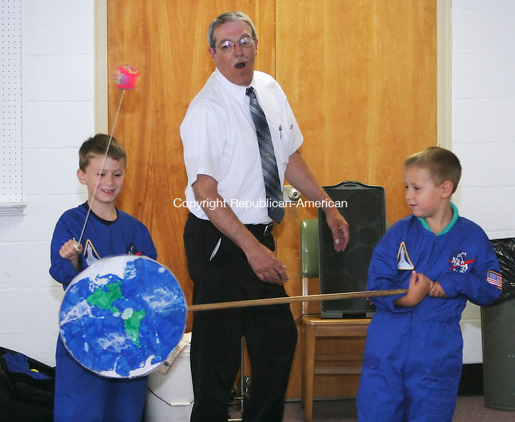 SEYMOUR, CT 7/31/07- 073107BZ04- From left- Tyler Pranger, 6, of Oxford, Aerospace educator Gary Pozzato, a retired engineer at Hamilton Standard, and Zachary Pranger, 10, of Oxford, do an experiment demonstrating orbit during &quot;Go For The Stars&quot; at the Seymour Public Library Tuesday.  The program, conducted by Pozzato, included a power point presentation with video clips and featured hands on experiments explaining scientific principles related to space travel.<br /> Jamison C. Bazinet Republican-American