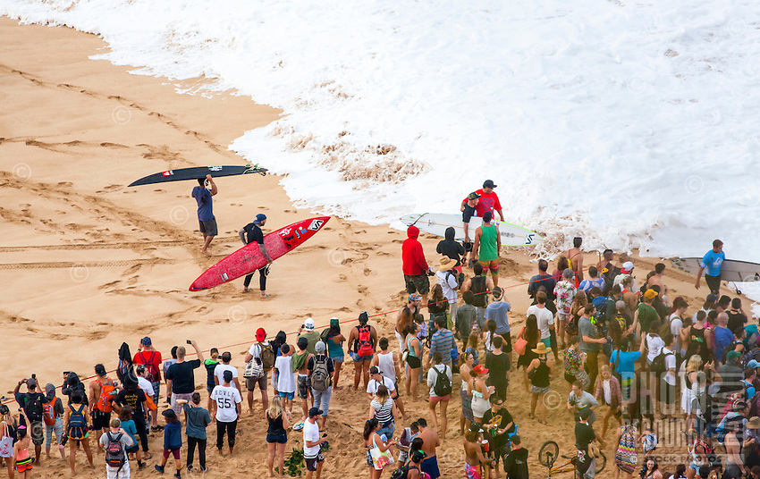 A crowd of spectators watch as competitors prepare to paddle out at the 2016 Big Wave Eddie Aikau Contest, Waimea Bay, North Shore, O'ahu.