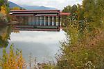 Idaho, Bonner County, Sandpoint. Sandpoint's Landmark Cedar Street Bridge reflecting in Sand Creek in Autumn.