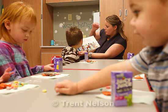 Angie Knaphus reads a story to children at snack time in the Central Utah Public Health Department's Early Intervention Program Wednesday, November 18 2009 in Richfield. Left to right Jayden Julander, Riddick Thayne, Gavin Julander. Children up to three years old who may have developmental delays or disabilities are helped with problem solving and learning as part of the program.