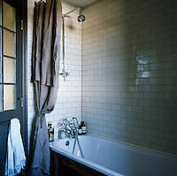 A simple tiled bathroom. A curtain of Swedish linen cunningly conceals a plastic shower curtain next to the bath.