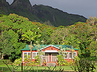 A red plantation Anahola Japanese Association building with tropical trees and a misty mountain background on Kaua'i.