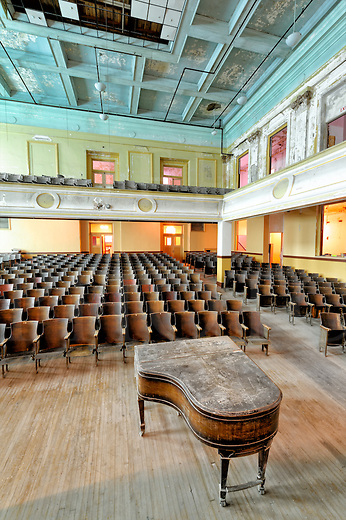 This is a large unused high school auditorium with a high sky-blue ceiling, an empty field of seats, and one lone grand piano in residence waiting for some music lovers to come visit once again. The school was built in 1917 with the grand piano being bought brand new for it, and hasn&rsquo;t moved from the building since. It is in the same rough and dusty condition as the room with balconies it lives in, and is unplayable nowadays with a few missing keys and an old age case of wobbly wooden legs. This shot was taken from the auditorium stage, the view every high school actor has seen.<br /> <br /> This eastern Pennsylvania school is in anthracite coal country and closed in 1980, never to be used in education again. It is now being attempted to re-purpose it as a general community center and it&rsquo;s been slow going in an economically depressed area, but at least it isn&rsquo;t a hollowed out and ransacked shell thanks to some people who care and try.<br /> <br /> Monthly Newsletter sign up at Dierks Photo on Facebook...