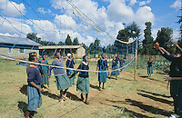 Kenya. Rift Valley Province. Mwenja. Primary school. After school, the tudents, girls and boys, play games on the grass and make sports, like volley-ball. The pupils are wearing a green, blue and and orange uniform. © 2004 Didier Ruef