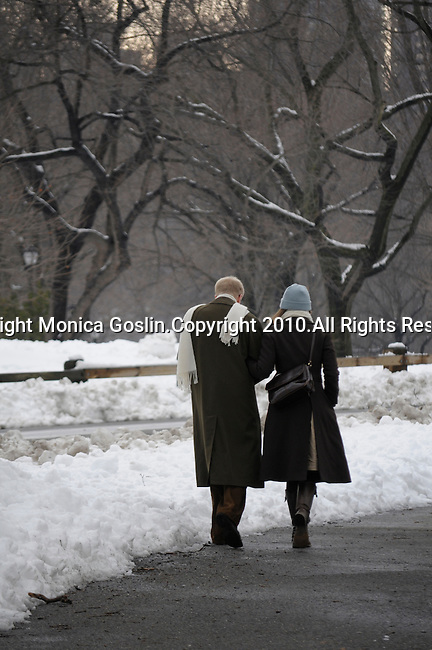A couple walks through a snowy Central Park in New York City.