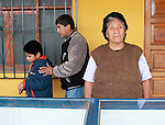 Ronald's father Jaime Fuentes guides Ronald, 9 behind his grandmother at their family store in Petrol, Peru.