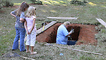Eight-year-old Elizabeth Cuchens, left, and 7 year-old Emily Richards watch as Robert Sculley digs the grave November 1, 2006 for fallen US Marine Lance Cpl Daniel B. Chaires in the back yard of the family home prior to his funeral and burial the following day.