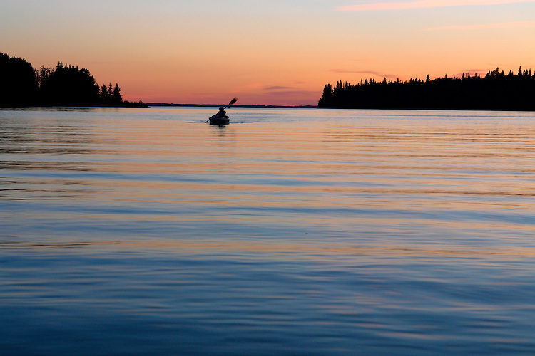 Kayaking on Clear Lake in the evening light Riding Mountain National Park, Manitoba, Canada.