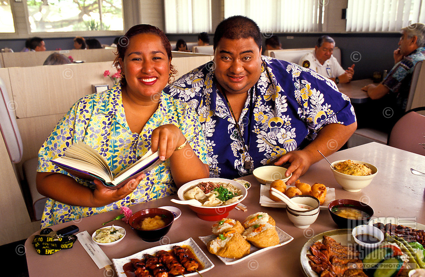 Lina Girl and Bruddah Sam, hosts of the now defunct cable show ìLocal Kine Grindsî, enjoying a feast of local foods at a Honolulu restaurant