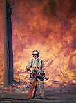A firefighter waits for the flow of water as a fire in Ybor City burns out of control May 19, 2000.  It went up like logs on a bonfire when flames licked the wooden frames of the apartments in The Park at Ybor City. Firefighters battled the inferno for hours. When it was over, five city blocks were leveled at a cost of about $40 million dollars.