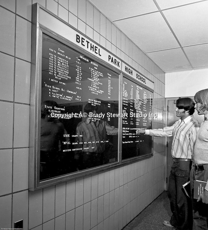 Bethel Park PA:  View of the new high school records case in the Gym Building Lobby.  Two students looking at the extensive list of Bethel Park Track & Field Records - 1973.