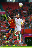 01.08.2012 Manchester, England. Spain midfielder Iker Muniain and Morocco midfielder Driss Fettouhi in action during the third round group D mens match between Spain and Morocco at Old Trafford.