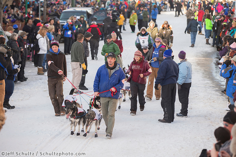 Paige Drobny is escorted to the line by volunteer handlers during the Iditarod 2014 Ceremonial start in downtown Anchorage, Alaska.<br /> <br /> Iditarod Sled Dog Race 2014<br /> PHOTO (c) BY JEFF SCHULTZ/IditarodPhotos.com -- REPRODUCTION PROHIBITED WITHOUT PERMISSION