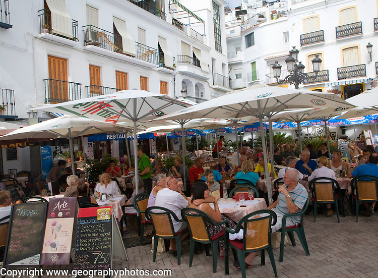 People sitting at restaurant tables outdoors in the village of Competa, Malaga province, Spain