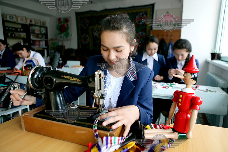 A girl sewing at a school in Ispisor Jamoat Village where youths aged 15 and 16 learn practical life skills.