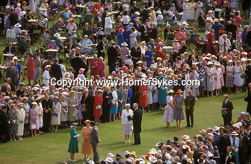 The Queens Garden Party Buckingham Palace  London.  The Queen in green dress left, greeting people who have been nominated to meet her.The English Season published by Pavilon Books 1987