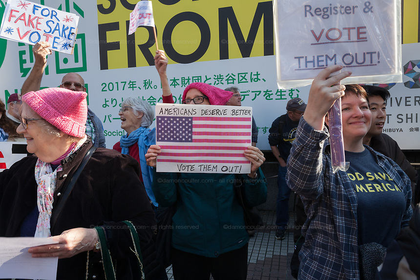 "A woman wears a pink pussy hat and holds a sign saying, Americans Deserve Better"" at the Vote Out the Scandal rally at Hachiko Square, Shibuya, Tokyo, Japan. Sunday November 5th 2017. Timed to coincide with President Trumps visit to Japan, About 120 Americans living in Japan and some local Japanese  protested together from 2pm to 4pm to encourage US citizens to register to vote in future elections and call on the US government to honour it responsibilities to the American people,."
