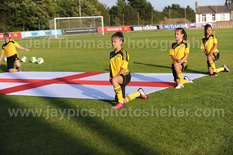 Ball girls unveil the England flag before the UEFA Womens U19 Championships at Stebonheath Park, Llanelli  Monday 19th August 2013. All images are the copyright of Jeff Thomas Photography-www.jaypics.photoshelter.com-07837 386244-Any use of images must be authorised by the copyright owner.