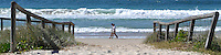 Two people walk along Miami Beach on Queensland's Gold Coast.